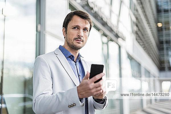 Porträt eines Geschäftsmannes mit Smartphone in der Stadt