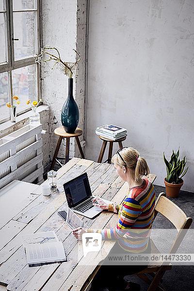 Frau sitzt mit Laptop und Tablett am Schreibtisch in einem Loft