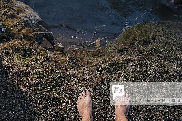 Füße eines am Seeufer stehenden Mannes