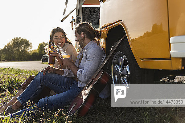 Affectionate couple on a road trip  taking a break  drinking soft drinks