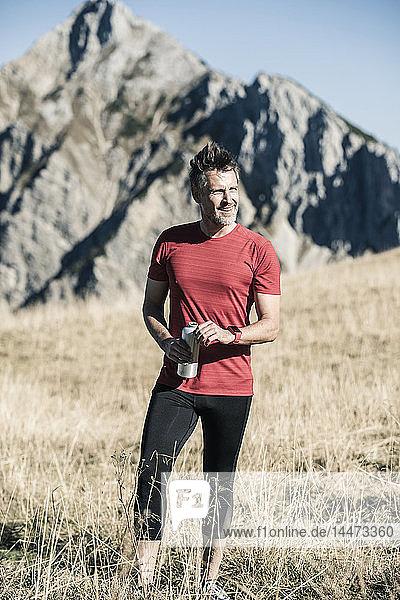 Österreich  Tirol  lächelnder Athlet auf Almwiese stehend
