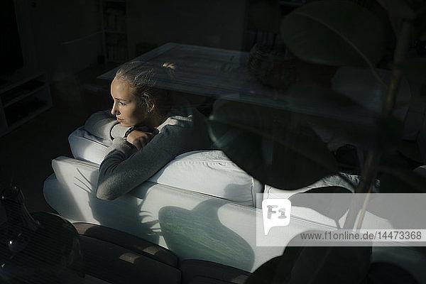 Ernsthaftes Teenager-Mädchen sitzt zu Hause auf der Couch und schaut aus dem Fenster