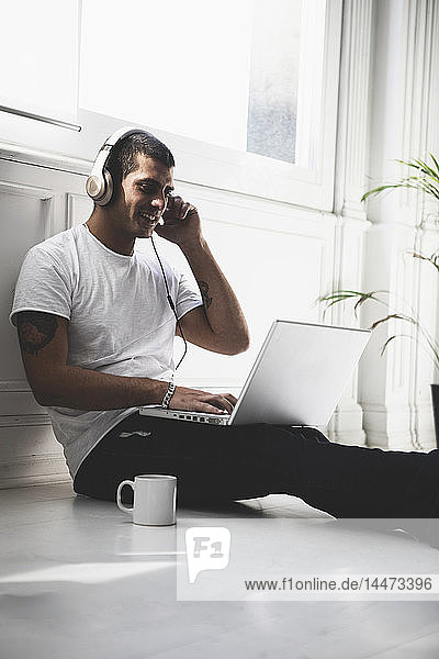 Smiling young man with headphones sitting on the floor using laptop