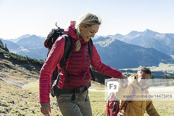 Österreich  Tirol  lächelndes Paar wandert Hand in Hand in den Bergen
