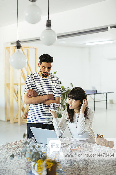 Two colleagues working together at table with laptop