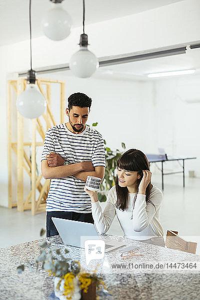 Zwei Kollegen arbeiten gemeinsam am Tisch mit Laptop