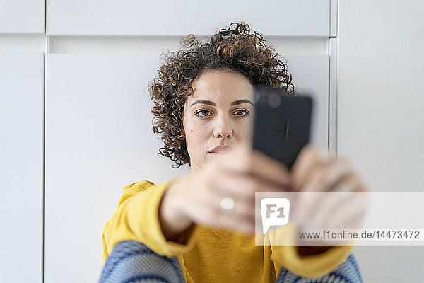 Frau benutzt Mobiltelefon zu Hause