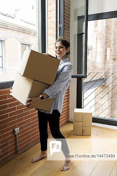 Porträt einer lächelnden jungen Frau mit Karton in neuer Wohnung am Fenster