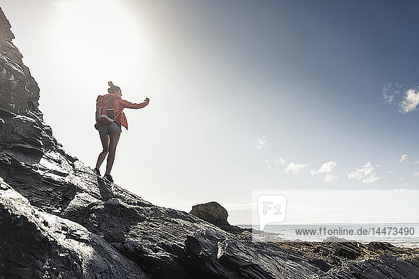 Young woman hiking on a rocky beach  taking pictures with her smartphone