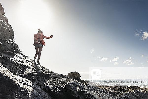 Junge Frau wandert an einem felsigen Strand und fotografiert mit ihrem Smartphone