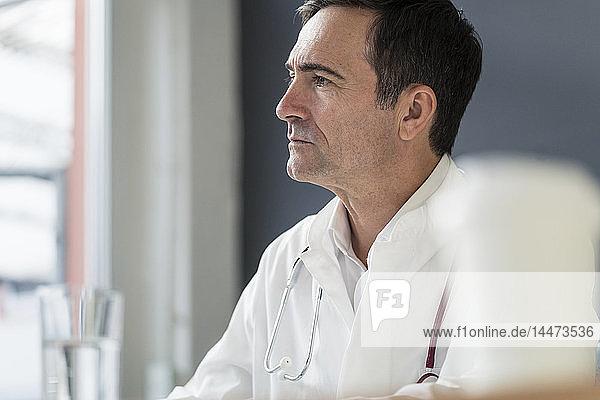 Porträt eines nachdenklichen Arztes in der medizinischen Praxis mit Blick zur Seite