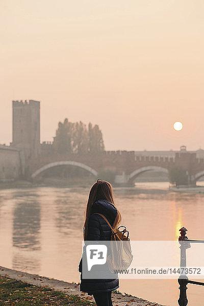 Italien  Verona  Rückenansicht einer Frau mit Rucksack beim Blick in den Sonnenuntergang