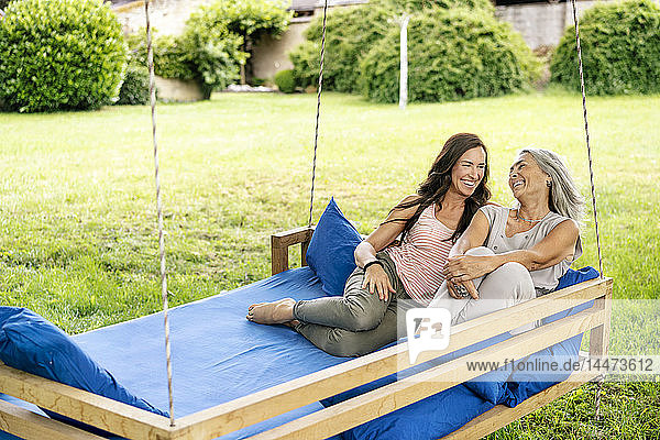 Two happy women relaxing on a hanging bed in garden