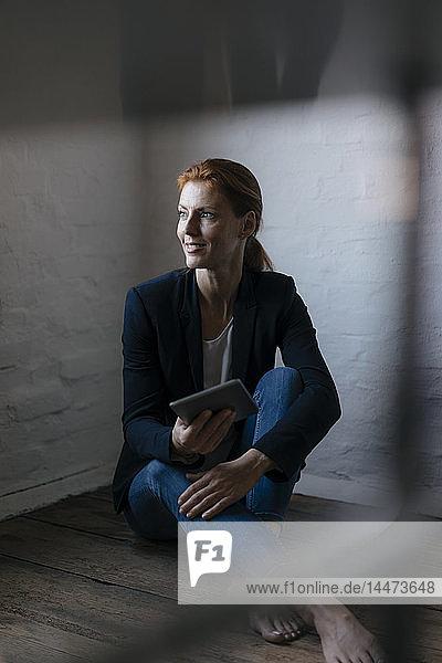 Barfüßige Geschäftsfrau sitzt im Büro mit Tablett auf dem Boden