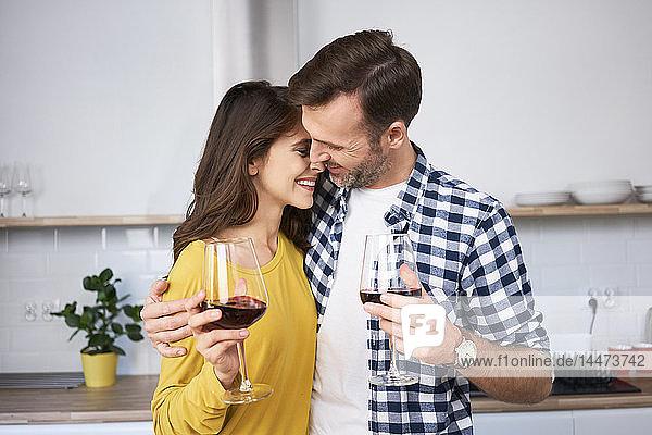 Glückliches Paar steht in der Küche  umarmt  trinkt Rotwein  küsst sich