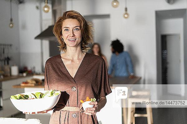 Freunde bereiten in der Küche ein Abendessen vor  Frau serviert Salat