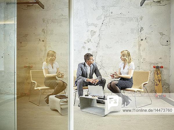 Geschäftsmann und Geschäftsfrau im Gespräch im modernen Büro