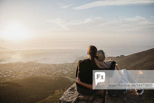 South Africa  Cape Town  Kloof Nek  two women sitting on rock at sunset