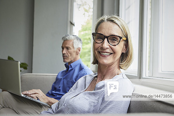 Portrait of smiling mature woman on couch with man in background using tablet