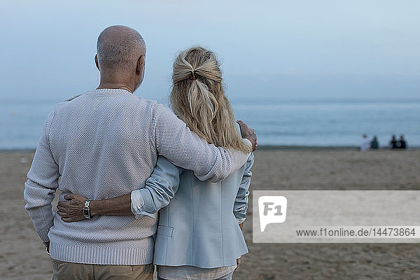 Spain  Barcelona  rear view of senior couple embracing on the beach at dusk