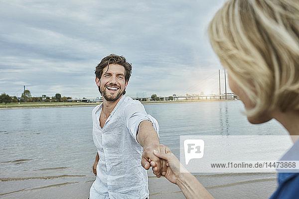 Deutschland  Düsseldorf  glückliches junges Paar am Rheinufer
