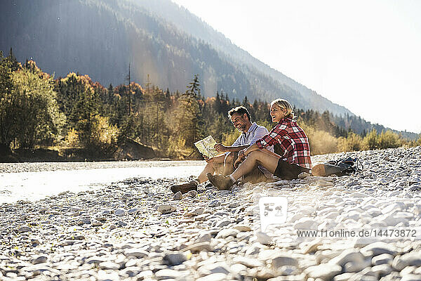 Austria  Alps  couple on a hiking trip having a break at a brook reading map