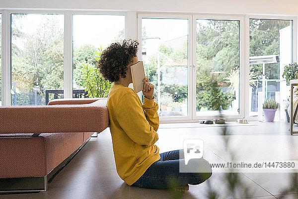 Frau mit Buch sitzt zu Hause auf dem Boden