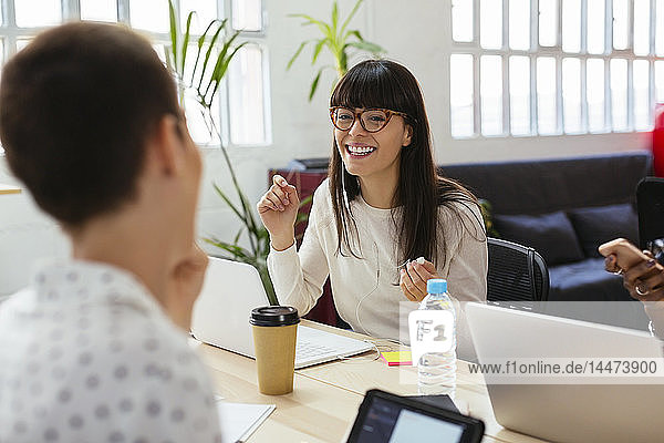 Colleagues working at desk in office smiling at each other