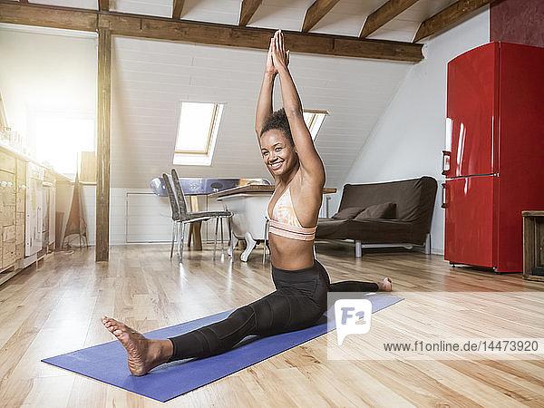 Porträt einer glücklichen jungen Frau in Yoga-Pose beim Spagat