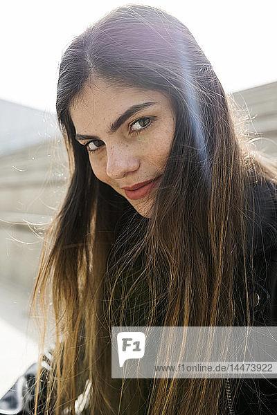 Porträt einer selbstbewussten jungen Frau mit langen braunen Haaren im Freien