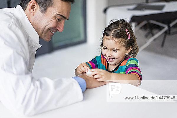 Arzt mit Gips und glückliches Mädchen am Schreibtisch in der Arztpraxis