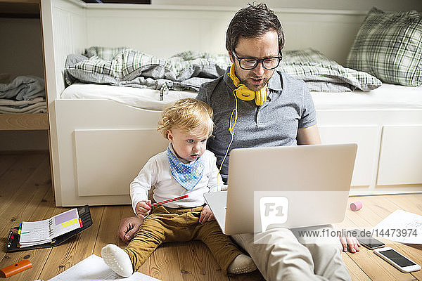 Father at home with his little son and laptop