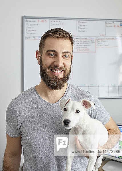 Portrait of smiling man in the office with his dog