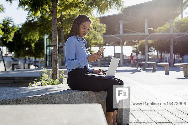Geschäftsfrau mit Laptop und Smartphone