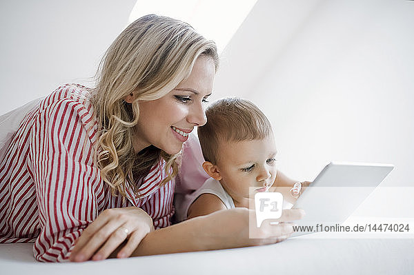 Smiling mother and toddler son lying in bed at home using tablet