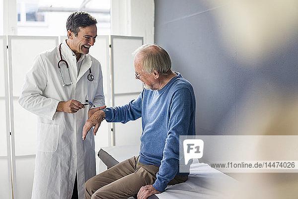 Glücklicher Arzt untersucht älteren Patienten in medizinischer Praxis