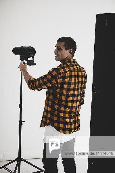 Photographer adjusting lighting equipment in studio