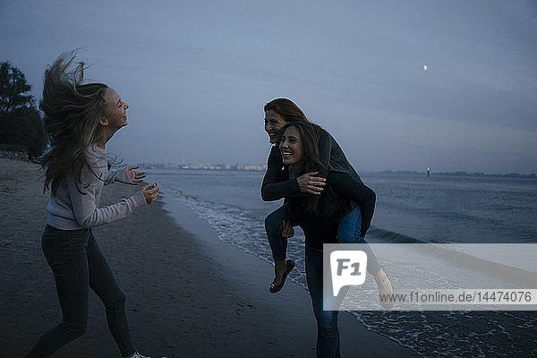 Deutschland  Hamburg  sorgenfreie Mutter mit zwei Teenager-Mädchen nachts am Strand am Elbufer