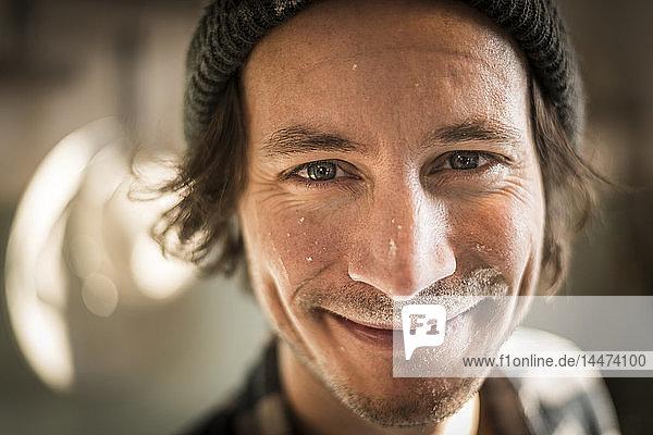 Porträt eines kochenden Mannes mit Mehl im Gesicht