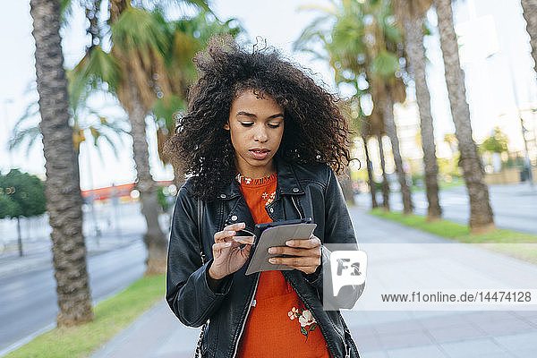 Junge Frau benutzt digitales Tablet im Freien