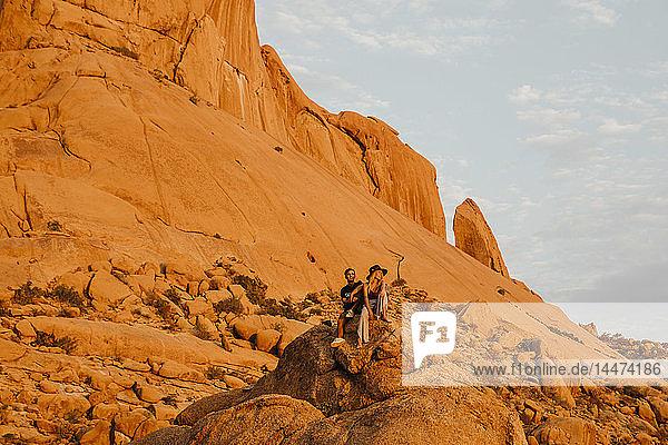 Namibia  Spitzkoppe  Ehepaar sitzt bei Sonnenuntergang auf einem Felsen