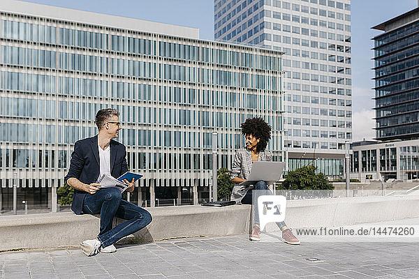 Zwei zuversichtliche Kollegen arbeiten vor dem Bürogebäude zusammen