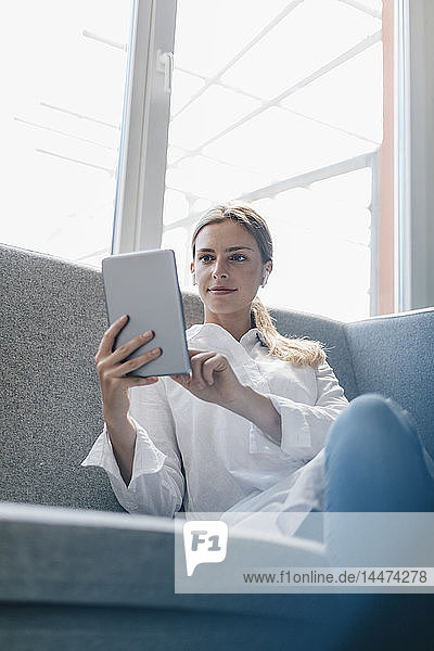 Junge Frau sitzt auf dem Sofa und benutzt ein digitales Tablett