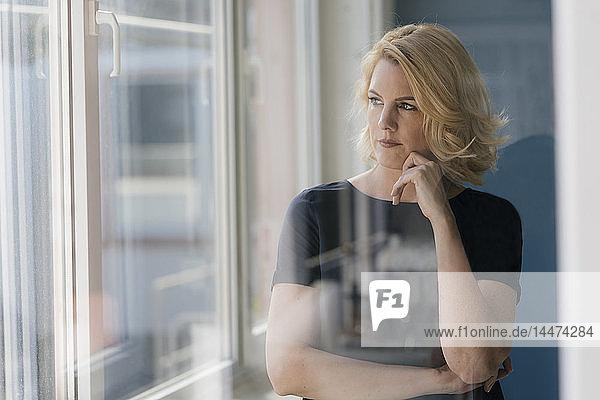 Seriöse blonde Frau  die aus dem Fenster schaut
