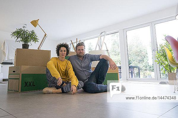 Porträt eines im Wohnzimmer sitzenden Paares mit Pappkartons