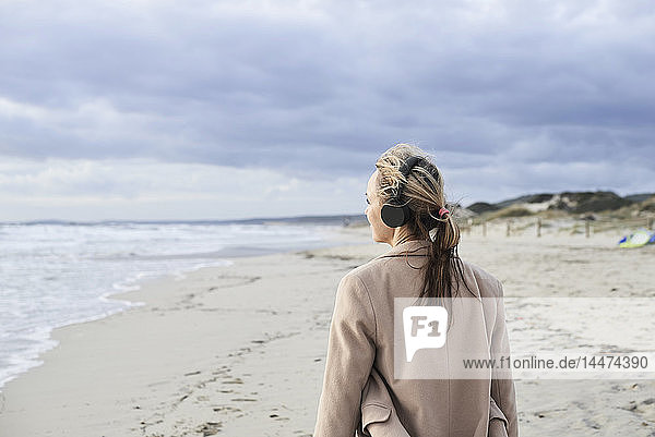 Spain  Menorca  back view of senior woman listening music with wireless headphones on the beach in winter