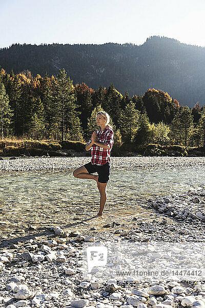 Austria  Alps  woman practicing yoga in a mountain brook