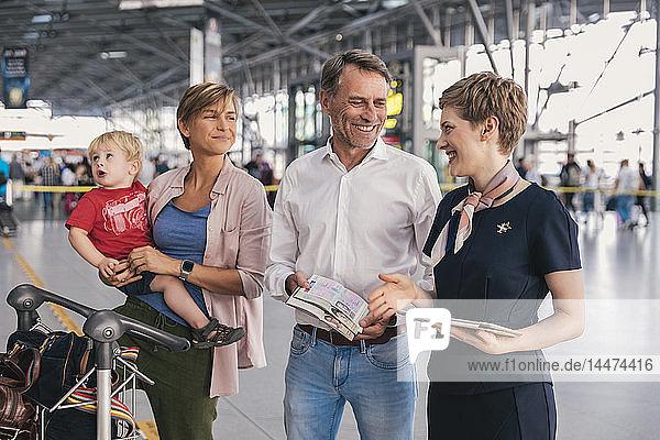 Glückliche Familie zeigt dem Mitarbeiter einer Fluggesellschaft am Flughafen ihre Pässe