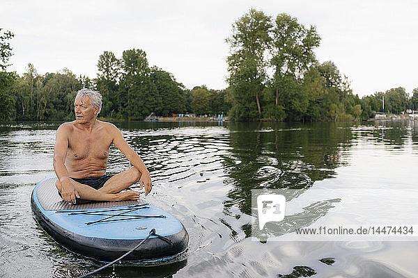 Senior man sitting on SUP board on a lake