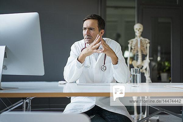 Seriöser Arzt am Schreibtisch sitzend in medizinischer Praxis mit Skelett im Hintergrund